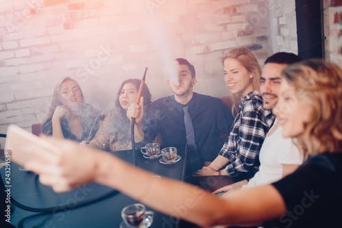 Hookah smoking shisha in bar and nightclub, team of friends