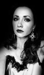 Frau mit großen Kreuz-Ohrringen vor schwarzem Hintergrund