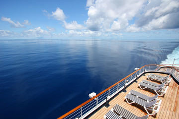 Cruise ship sails across a beautiful calm ocean.
