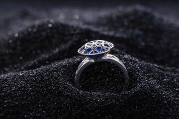 Diamond shape silver ring with blue gemstones on black sand. Modern fashion jewelry