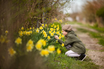 Teenager girl in green jacket and khaki beret near the daffodils' garden in the country. Spring farm and Easter theme
