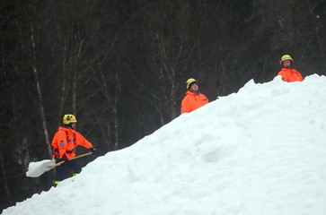 Members of the THW clear a roof from heavy snow in Berchtesgaden