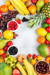 Frame made of ripe fruits, strawberries raspberries oranges plums apples kiwis grapes blueberries mango persimmon on the white table, top view, copy space for text, selective focus