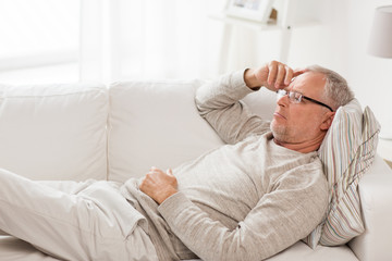 old age, problem and people concept - senior man  lying on sofa and thinking at home