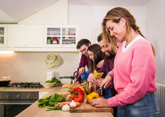 Group of caucasian friends having fun cooking togheter pasta and vegetables