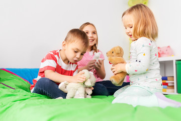 childhood, leisure and people concept - happy children playing with soft toys at home