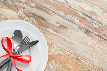 valentines day, table setting and festive dinner concept - plate with spoon, knife and fork tied with red ribbon on wooden background from top