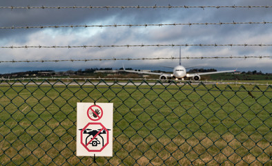 No drone sign on fence of airport runway, Passenger aircraft taxiing on runway in the background Wall mural