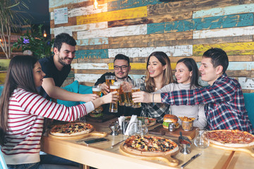 Happy young friends celebrating with pizza and drinking beer at bar restaurant - Friendship concept with young people enjoying time together and having genuine fun at rustic pizzeria - cheers