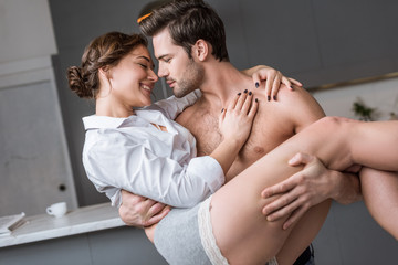 passionate man holding in arms smiling girlfriend at home Wall mural