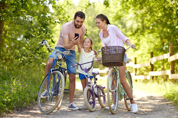 family, leisure and technology concept - happy mother, father and little daughter with smartphone and bicycles in summer park Wall mural