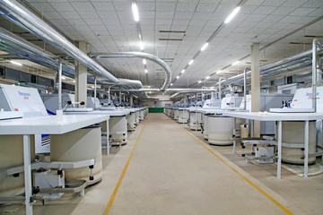 Spinning machinery parts and white plastic buckets in the factory
