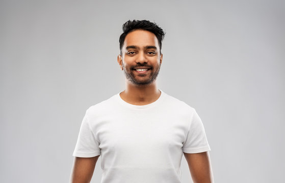 people concept - smiling young indian man over gray background