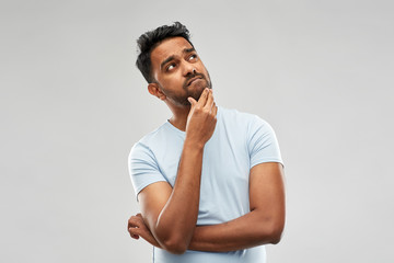 doubts and people concept - houghtful indian man touching his beard and looking up over grey background