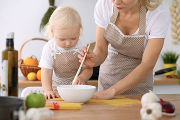 Poster Cuisine Happy mother and little daughter cooking in kitchen. Spending time all together, family fun concept