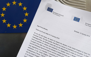 A copy of the letter send by EU Council President Donald Tusk and EU Commission President Jean-Claude Juncker to British Prime Minister Theresa May is seen next to an European Flag in this illustration picture