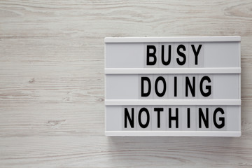 Modern box with text 'Busy doing nothing' on a white wooden background, top view. From above, flat lay, overhead. Copy space. Wall mural