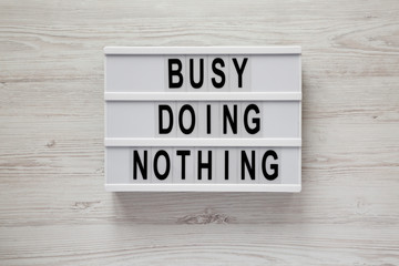 Lightbox with text 'Busy doing nothing' on a white wooden background, top view. From above, flat lay, overhead.
