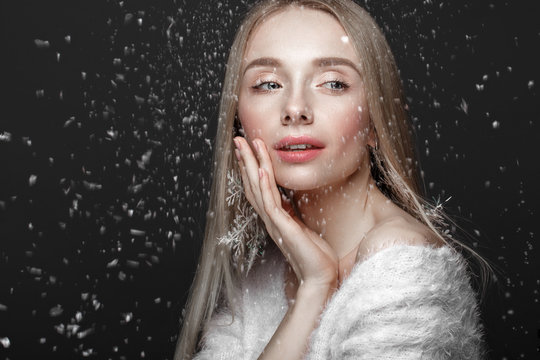 Beautiful blonde girl in a winter image with snow. Beauty face.