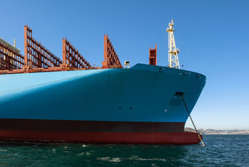 The bow of a huge container ship at anchored in the roads.