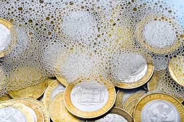 Money-laundering. Coins are washed in soapy water. Taxes and Finance