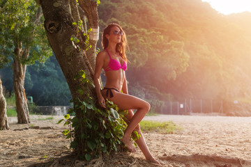 Full-length portrait of fit young woman in pink bra and black panties sitting on tree trunk wearing sunglasses with green jungles in background