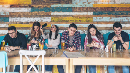 Group of friends using smartphone at rustic restaurant - Young hipster people addicted by mobile phone on social network community - Technology concept with connected millennials - focus on center guy