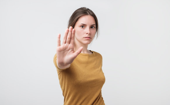 Young european woman standing with outstretched hand showing stop gesture