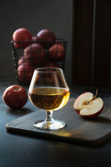 Glass with Calvados brandy and red apples on black.