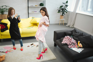 Small blonde girl taking picture of her friend on camera in room. Brunette posing and looking down. Both teenagers wear clothes and shoes for adult women.
