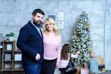 Happy family dress up a christmas tree. Family decorates the Christmas tree.