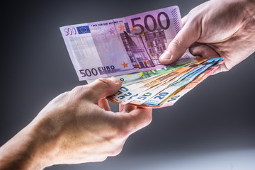Male hands holding euro banknotes and the other hand to receive a bribe