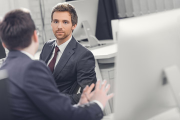 selective focus of businessmen talking while working together in office