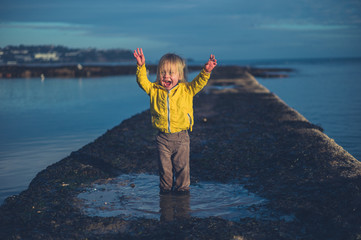 Happy toddler standing in rock pool at sunset