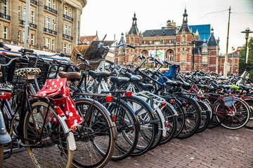 View of bicycles along street in Amsterdam with historic Stadsschouwburg building in the background