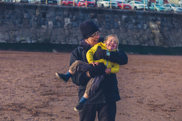 Toddler playing with grandfather on beach