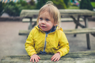 Little toddler sitting on bench outside