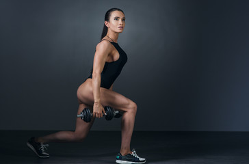 beautiful athletic young woman with muscles doing exercises with dumbbells bodybuilding