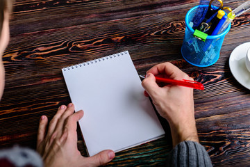 Close up of man's hands with pencil writing on notebook mockup