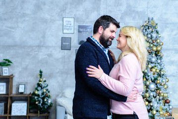 Husband and wife are dancing in front of a Christmas tree. A man and a woman are dancing in front of a New Year tree. A man confesses his love to a girl.