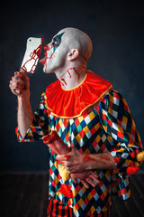 Scary bloody clown licks the knife blade