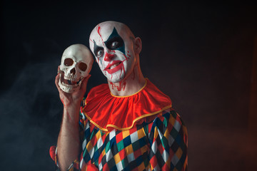 Bloody clown with crazy face holds human skull