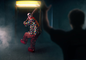 Bloody clown with baseball bat against his victim