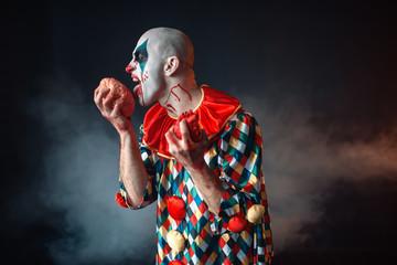Mad bloody clown licks human brain