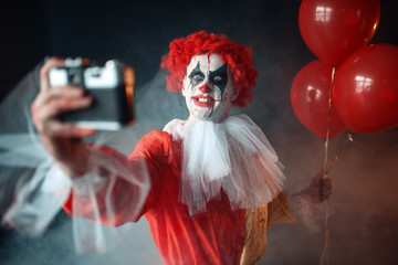 Scary bloody clown with crazy eyes makes selfie