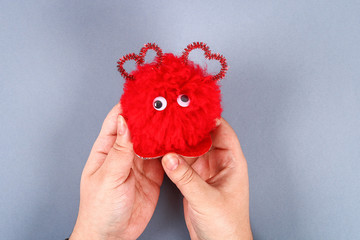 Red handmade diy monster pom pom from yarn, chenille stems in shape heart.