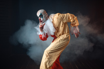 Mad bloody clown sneaks and shows the quiet sign
