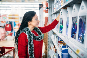 Woman looks on christmas gifts in supermarket