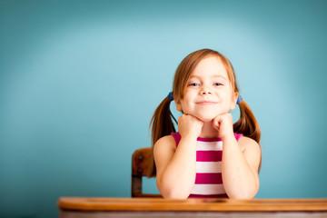 Happy Little Girl Sitting in School Desk - Room for Text