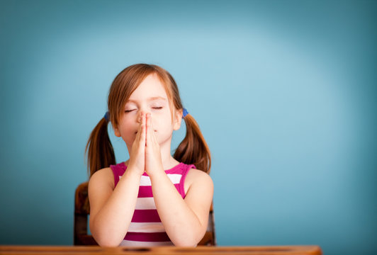 Little Girl Praying While in School Desk - Room for Text